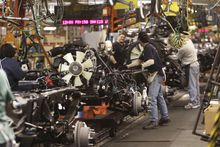 An engine is joined to the chassis on the Silverado and Sierra heavy-duty pickups assembly line at the Flint Assembly in Flint, Mich. General Motors Co. will pay more than $189 million in profit-sharing. (Associated Press)