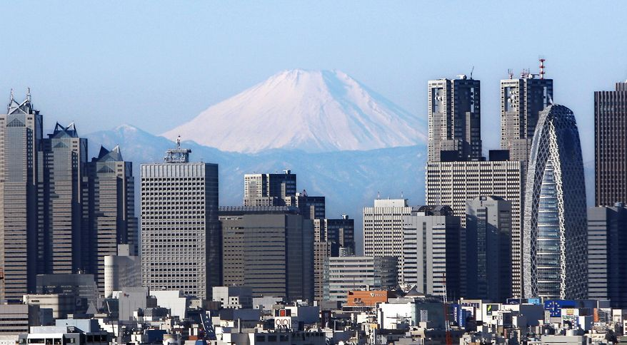 Japan's highest peak, Mount Fuji, looms over high-rise buildings of Tokyo's Shinjuku district on Jan. 16, 2009. Japan confirmed Monday Feb. 14, 2011, that China's economy surpassed its own as the world's second largest in 2010 and said a late-year downturn was Japan's first quarterly contraction in more than a year. (AP Photo/Kyodo News, File)