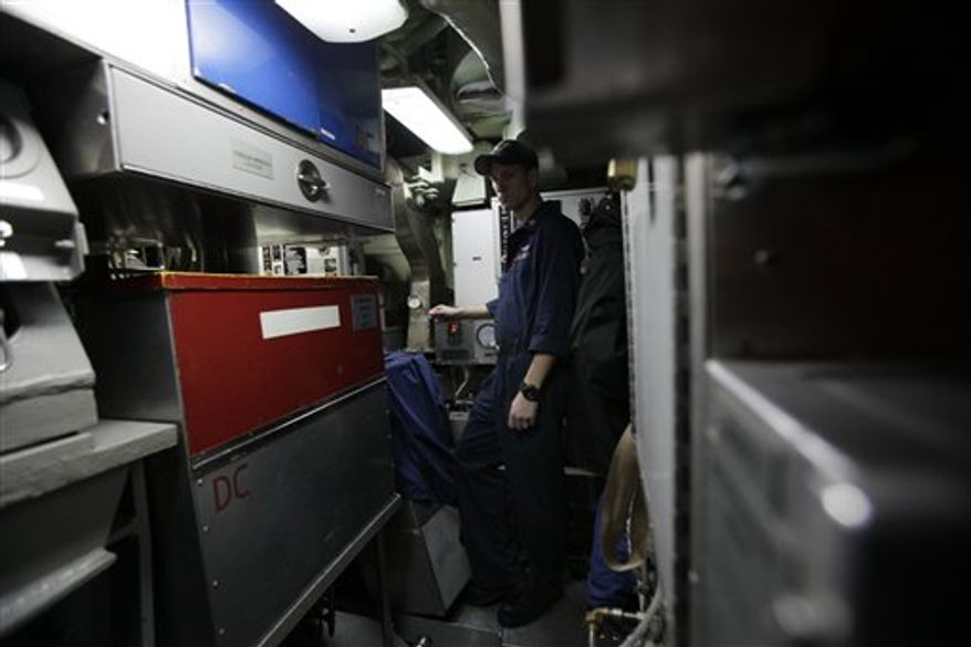 In this photo taken Friday, Feb. 11, 2011, Petty officer Luke Riblet, of Coco Beach, Fla., stands in the former smoking area in the engine room of the USS Charlotte, a nuclear powered attack submarine, at the Yokosuka Naval Base south of Tokyo. As of January all submarines in the U.S. Navy are officially smoke free, and it's been a tense transition.  (AP Photo/Greg Baker)