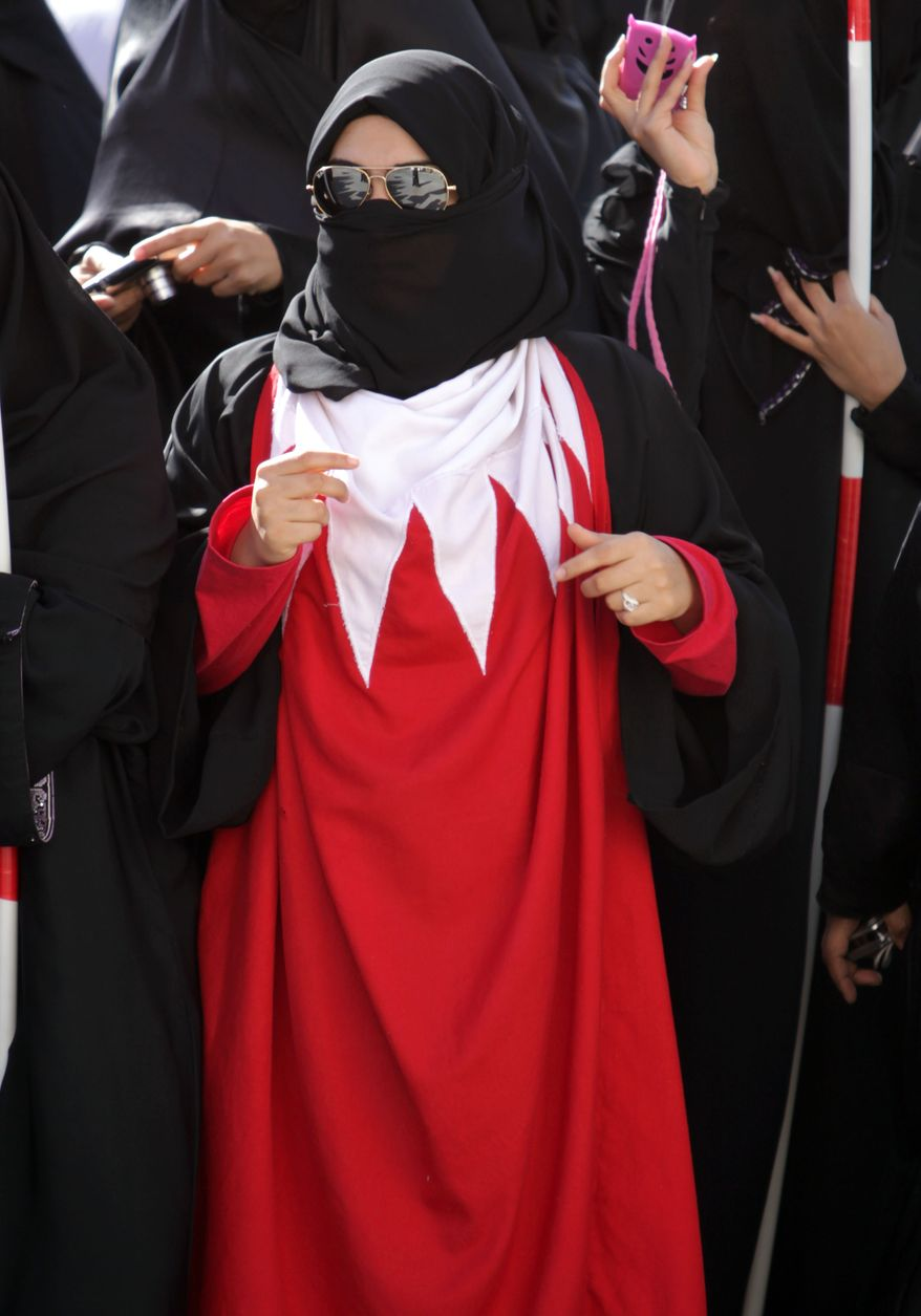 A Bahraini woman wears a Bahraini flag Monday, Feb. 14, 2011, during an anti-government demonstration in the village of Duraz, Bahrain, outside the capital of Manama. (AP Photo/Hasan Jamali)