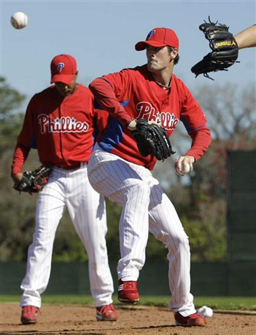 Philadelphia Phillies' Jimmy Rollins, right, throws to first base during spring training baseball practice, Wednesday, Feb. 23, 2011, in Clearwater, Fla.  Pete Orr is at left. (AP Photo/Eric Gay)