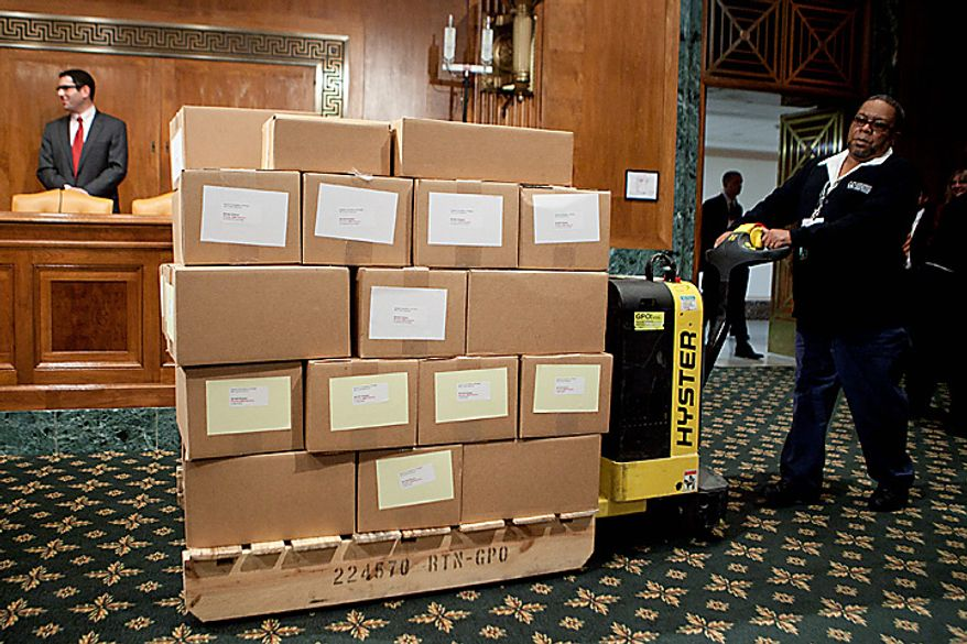 **FILE** Glen Perkins delivers copies of the fiscal 2012 budget to the Senate Budget Committee hearing room in Washington on Feb. 14. (Bloomberg)