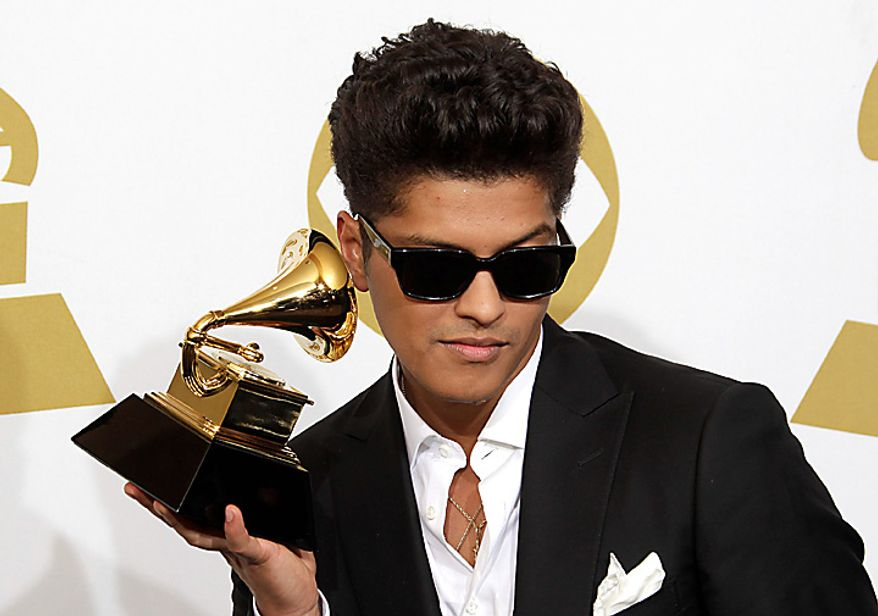 Bruno Mars poses backstage with the award for best male pop vocal performance at the 53rd annual Grammy Awards on Sunday, Feb. 13, 2011, in Los Angeles. (AP Photo/Jae C. Hong)