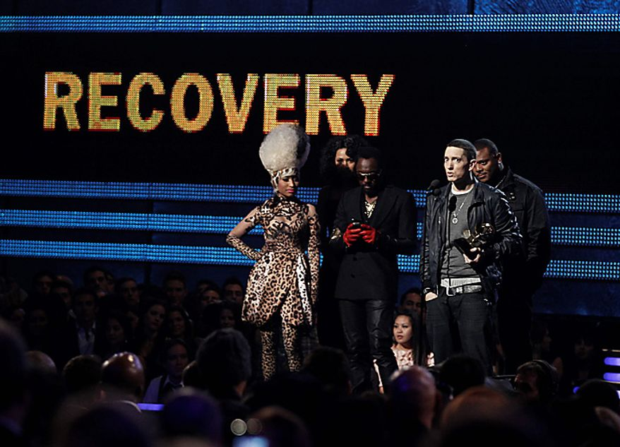 Eminem, right, accepts the award for best rap album as Nicki Minaj, left, and will.i.am, center, look on at the 53rd annual Grammy Awards on Sunday, Feb. 13, 2011, in Los Angeles. (AP Photo/Matt Sayles)