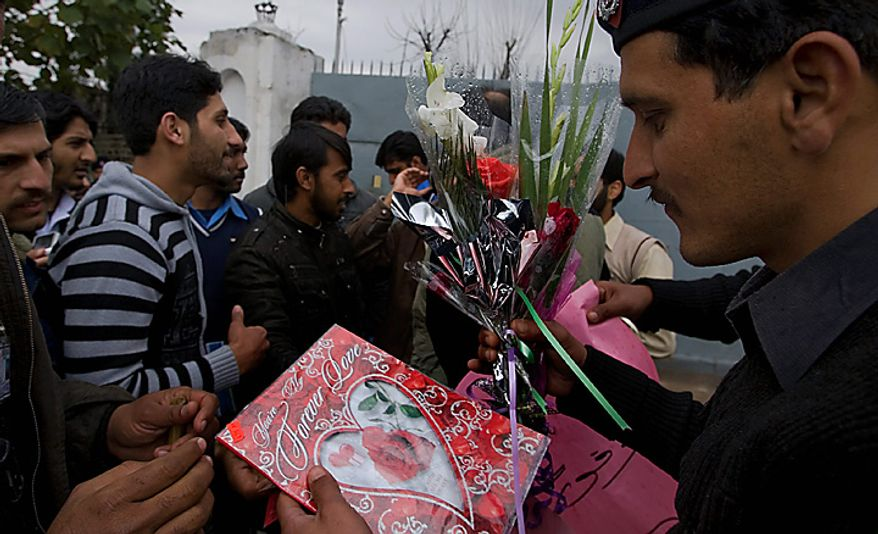 "A Pakistani police officer receives flowers and Valentine's Day cards for Mumtaz Qadri, the confessed killer of a liberal Pakistani governor, given by students during a rally outside the Adiala Jail, where Qadri's special court hearing was held on Monday, Feb. 14, 2011, in Rawalpindi, Pakistan. Qadri pleaded guilty to murder, telling a judge he didn't regret gunning the politician down because he killed ""an apostate,"" as required under his interpretation of Islamic law, lawyers said. (AP Photo/Anjum Naveed)"
