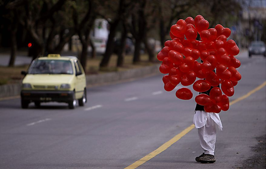A Pakistani vendor selling balloons for Valentine's Day waits for customers along a roadway in Islamabad, Pakistan, on Monday, Feb. 14, 2011. (AP Photo/Muhammed Muheisen)