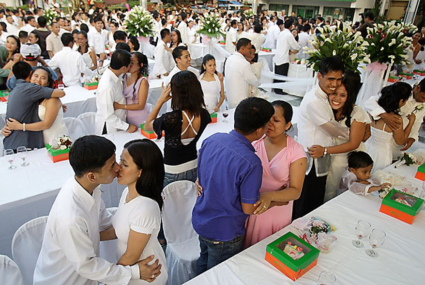 Newlywed Filipino couples kiss during ceremonies at a mass wedding in the suburban city of Taguig, south of Manila, as they celebrate Valentine's Day on Monday, Feb. 14, 2011. About 140 couples wed in the nuptials, sponsored by local government officials. (AP Photo/Aaron Favila)