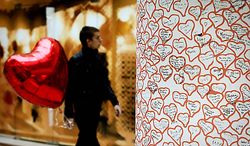 A man carries a red-heart balloon for Valentine's Day as he passes by a column decorated with hearts in Sofia, Bulgaria, on Monday, Feb. 14, 2011. Valentine's Day, named after the Christian patron saint for lovers, has gained popularity in Orthodox-dominated Bulgaria over the past few years. (AP Photo/Valentina Petrova)