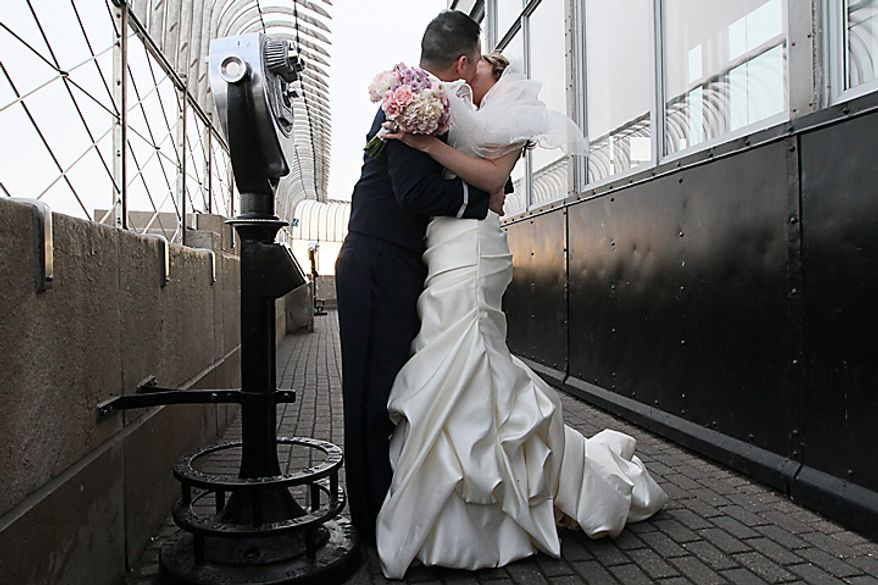 Air Force Capt. John Wu and Stephanie Hull, both of Louisville, Ky., kiss as they pose for photographers after being wed on Monday, Feb. 14, 2011, on the 86th floor of the Empire State Building in New York. The two, the grand-prize winners in the 17th annual Empire State Building and TheKnot.com Valentine's weddings event, joined 13 other couples from around the country in exchanging vows at the Big Apple's tallest building. (AP Photo/Tina Fineberg)