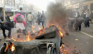 Demonstrators set a garbage can on fire in Tehran to show their displeasure with Iran's theocratic rulers on Monday, Feb. 14, 2011. This photo was obtained from an anonymous photographer. (AP Photo)