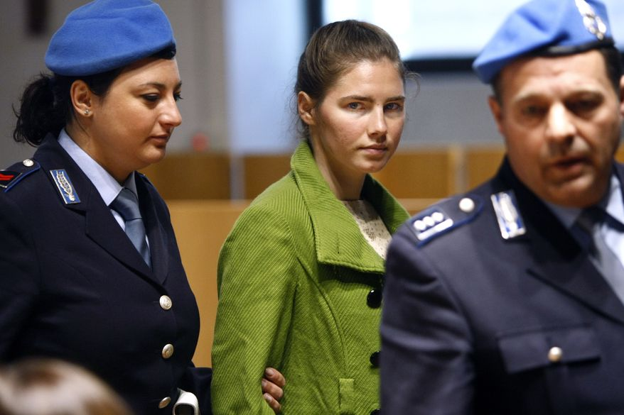American student Amanda Knox, who has been convicted of murder, is escorted by penitentiary police officers during a break in the trial at the court in Perugia, central Italy, on Dec. 3, 2009. Knox's parents were indicted for libel Tuesday, Feb. 15, 2011, for claiming their daughter had been abused by the Italian police. (AP Photo/Pier Paolo Cito, File)
