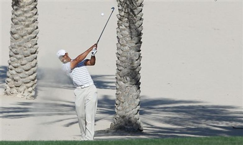 Tiger Woods of the US plays a shot from the rough on the 14th during the third round of the Dubai Desert Classic Golf Tournament at the Emirates Golf Club in Dubai, United Arab Emirates, Saturday, Feb.12, 2011.(AP Photo/Nousha Salimi)