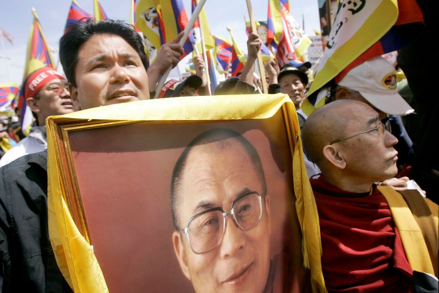 ** FILE ** Jigme K. Norbu (left), nephew of the Dalai Lama, here with Thupten Donyo (right), holds up a photo of the Dalai Lama as they rally with Tibetans and supporters at City Hall in San Francisco in April 2008. (AP Photo/Jeff Chiu, File)