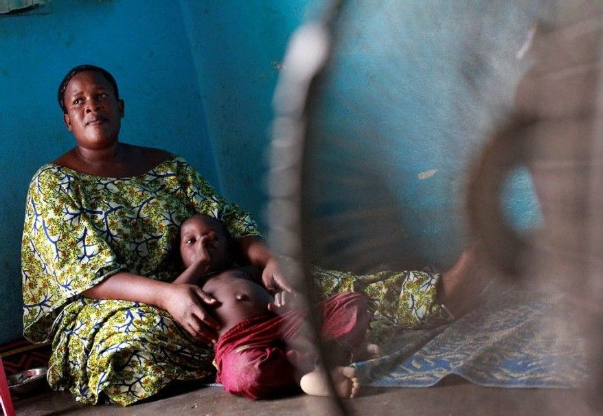 Diaby Madoussou holds one of her five children in their house in Abidjan. She has been waiting two months to have the body of her husband released to her. (Associated Press)