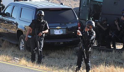 Mexican federal police guard a U.S. Embassy vehicle after it came under attack by unknown gunmen on Highway 57 between Mexico City and Monterrey, near the town of Santa Maria Del Rio, San Luis Potosi state, Mexico, Tuesday Feb. 15, 2011. A U.S. Immigration and Customs Enforcement agent was killed and another wounded in the attack.  (AP Photo/Pulso Diario de San Luis-Teodoro Blanco Vazquez)