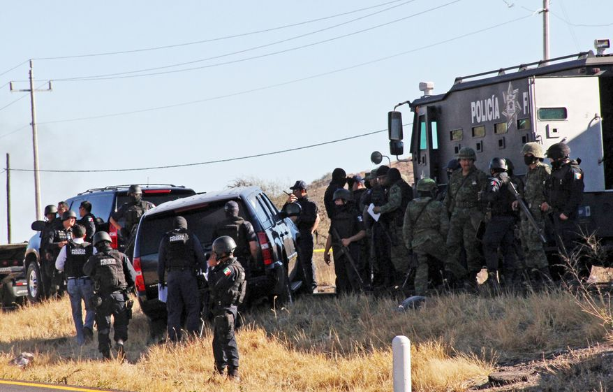 Mexican soldiers and federal police guard the U.S. Embassy vehicle in which one ICE agent was killed and another wounded in an attack Tuesday between Mexico City and Monterrey. (Associated Press)