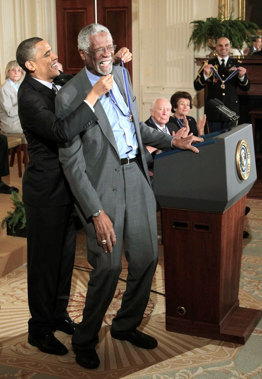 Mr. Obama reaches up to present a Presidential Medal of Freedom to basketball legend Bill Russell on Tuesday. Mr. Russell was one of 15 recipients. (Associated Press)