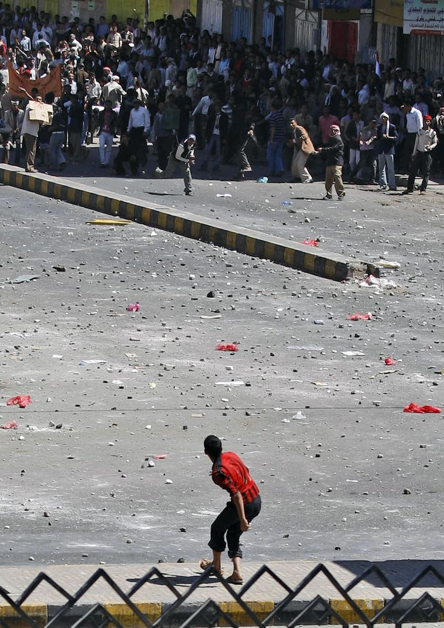 A supporter of the Yemeni government prepares to hurl a stone at anti-government demonstrators during clashes in Sanaa, Yemen, Thursday, Feb. 17, 2011. Police opened fire on protesters during clashes in a southern Yemeni port, killing two people, in the first known deaths in six days of Egypt-style demonstrations across the country's biggest cities, demanding the ouster of the president, a key U.S. ally in battling a Qaeda. (AP Photo/Hani Mohammed)
