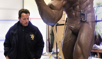 Arnold Schwarzenegger goes over every detail as he gets the first in-person-look at the larger-than-life clay sculpture artist Ralph Crawford is sculpting for him Wednesday, Feb. 16, 2011, in Lewiston, Idaho. Once complete the statue will be bronzed and sent to Austria to be displayed in Schwarzenegger's home town.(AP Photo/Lewiston Tribune, Kyle Mills)