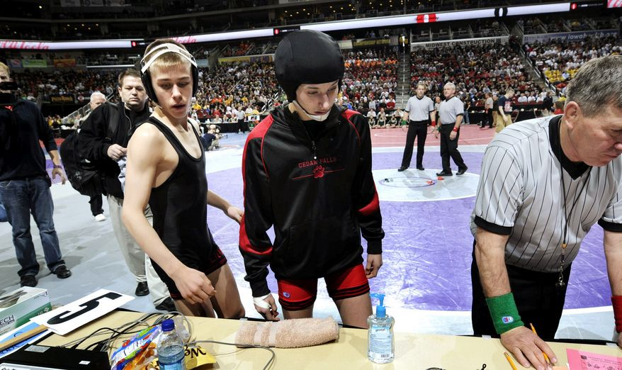 Cedar Falls' Cassy Herkelman and her opponent, Joel Northrup of Linn-Mar High, stand at the scorers table waiting for their leg bands prior to their Class 3A 112 pound first-round match at the Iowa State Wrestling tournament on Thursday in Des Moines. (Associated Press)