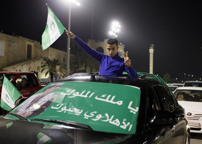 A supporter of Libyan President Moammar Gadhafi poses for the camera while holding a national flag during a pro-government demonstration in Tripoli, the Libyan capital, early on Thursday, Feb. 17, 2011. (AP Photo/Abdel Meguid al-Fergany)
