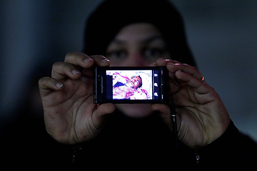 A Bahraini anti-government demonstrator shows a pictures of a wounded man who she said was injured during the riot police attack at Pearl Square in Manama, Bahrain, early Thursday morning, Feb. 17, 2011. Riot police firing tear gas and rubber bullets stormed a landmark square occupied by anti-government protesters Thursday, driving out demonstrators and destroying a makeshift encampment that had become the hub for demands to bring sweeping political changes to the kingdom. (AP Photo/Hassan Ammar)