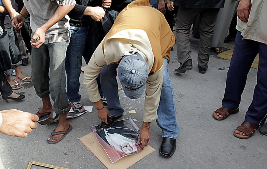A Bahraini anti-government demonstrator burns and stamps on a picture of King Hamad bin Issa Al Khalifa outside Salmaniya hospital in capital Manamaearly Thursday morning, Feb. 17, 2011. (AP Photo/Hassan Ammar)