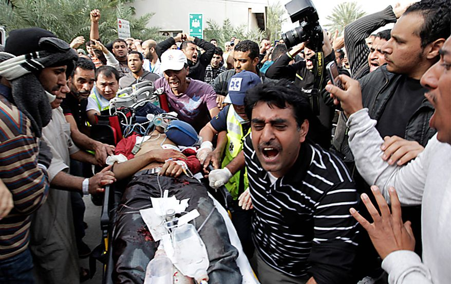 A Bahraini anti-government demonstrator lies injured on a stretcher as anti-government demonstrators take him to hospital in capital Manama early Thursday morning, Feb. 17, 2011. Armed patrols prowled neighborhoods and tanks appeared in the streets for the first time Thursday after riot police with tear gas and clubs drove protesters from a main square where they had demanded sweeping political change in this tiny kingdom. (AP Photo/Hassan Ammar)