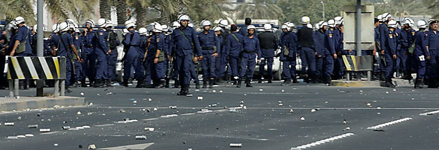 Bahraini riot police seen near Pearl Square during clashes with anti government protesters in capital Manama early Thursday morning, Feb. 17, 2011. Some protesters appeared unbowed as armed patrols prowled neighborhoods and tanks appeared in the streets for the first time Thursday after riot police with tear gas and clubs drove protesters from Pearl Square where they had demanded sweeping political change in this tiny kingdom. Medical officials said four people were killed. (AP Photo/Hassan Ammar)