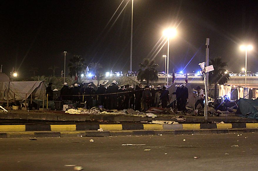 Bahraini riot policemen are seen after attacking peaceful demonstrators camping at Pearl Square in capital Manama early Thursday morning, Feb. 17, 2011. Riot police firing tear gas and rubber bullets stormed the landmark square occupied by anti-government protesters Thursday, driving out demonstrators and destroying a makeshift encampment that had become the hub for demands to bring sweeping political changes to the kingdom. (AP Photo/Hassan Ammar)