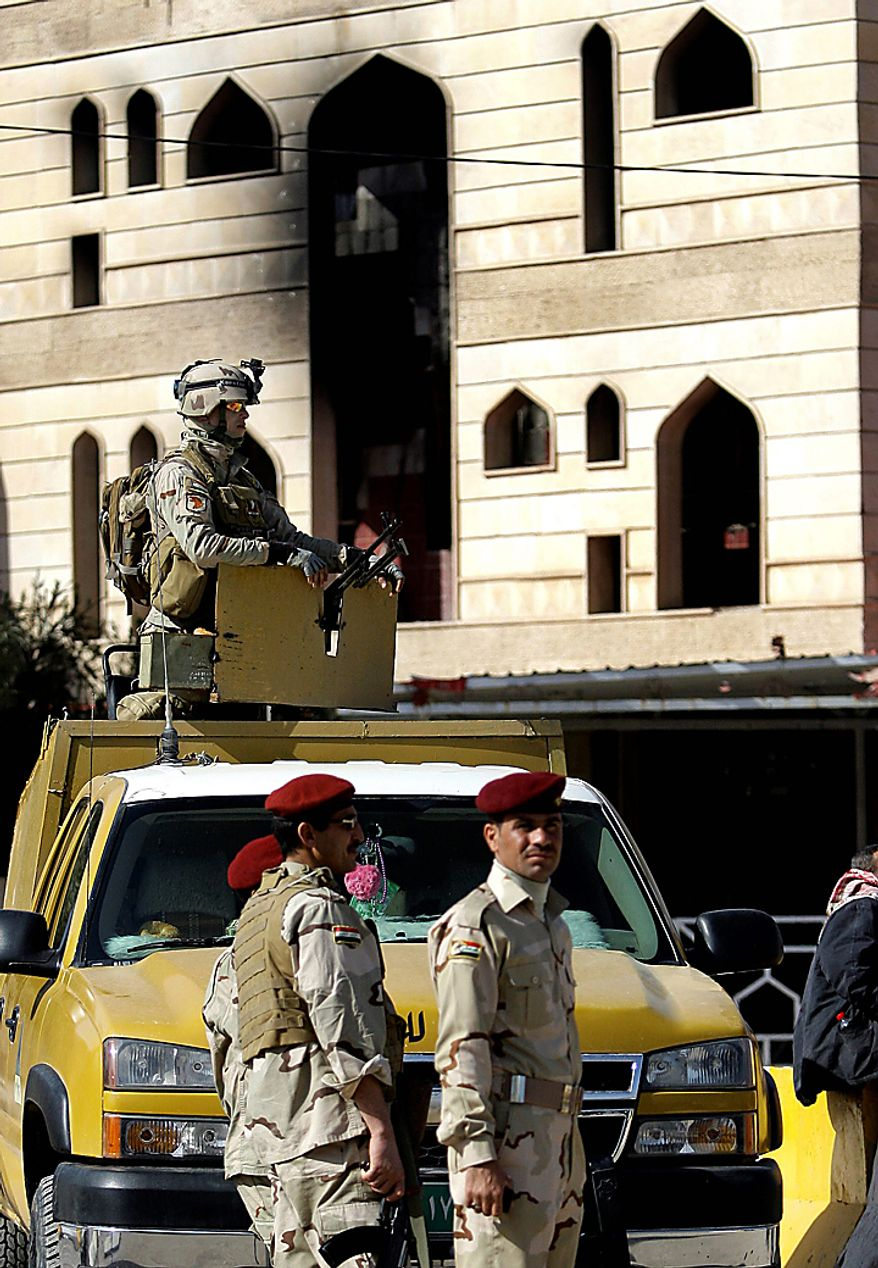 Iraqi security forces stand guard at the damaged provincial headquarters building in Kut, Iraq, Thursday, Feb. 17, 2011. About 2,000 stone-throwing demonstrators attacked local government offices on Wednesday, setting fire to a number of buildings, including the governor's house. (AP Photo/Hadi Mizban)