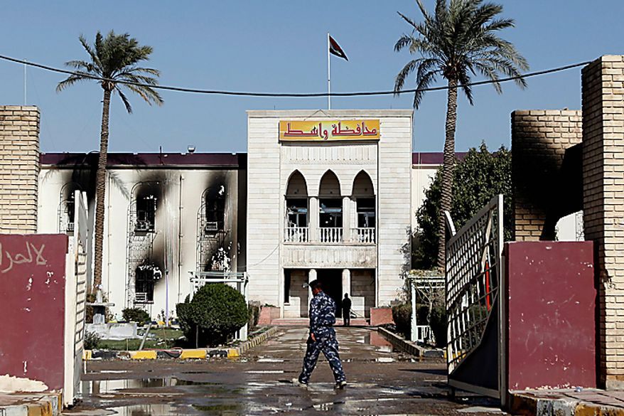 An Iraqi soldier enters the damaged provincial headquarters building in Kut, Iraq, Thursday, Feb. 17, 2011. On Wednesday about 2,000 stone-throwing demonstrators attacked local government offices, setting fire to some buildings, including the governor's house. (AP Photo/Hadi Mizban)