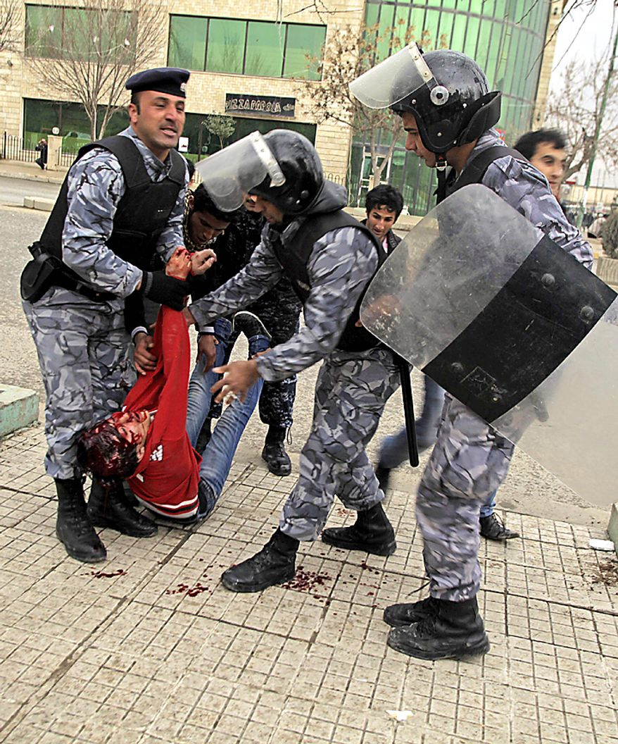 Iraqi riot police officers carry the body of a protester in front of the headquarters of Kurdish President Massoud Barzani's political party in Sulaimaniyah, 160 miles northeast of Baghdad Thursday, Feb. 17, 2011. Kurdish security forces opened fire on a crowd of protesters surrounding the headquarters of the party affiliated with the Kurdish president. (AP Photo/Yahya Ahmed)