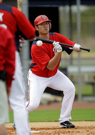 Washington Nationals starting pitcher Chien-Ming Wang of Taiwan goes through a bunt drill during a spring training workout on Thursday, Feb. 17, 2011, in Viera, Fla. (AP Photo/David J. Phillip)