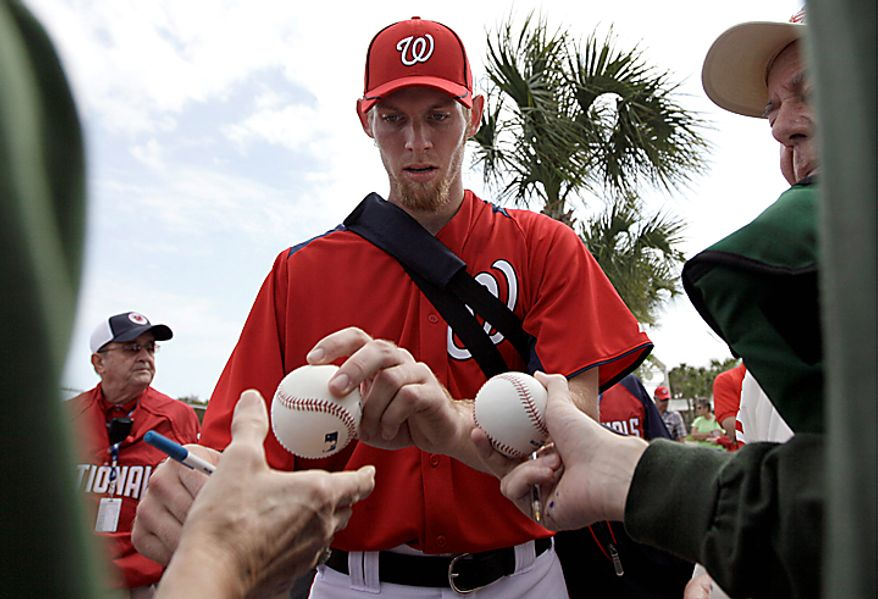 Washington Nationals pitcher Stephen Strasburg signs autographs for fans after a spring training baseball workout Thursday, Feb. 17, 2011, in Viera, Fla. (AP Photo/David J. Phillip)