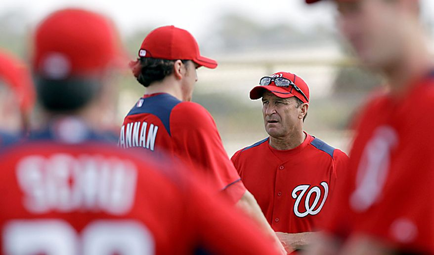 Washington Nationals manager Jim Riggleman, right, watches his team loosens up during spring training baseball Thursday, Feb. 17, 2011, in Viera, Fla. (AP Photo/David J. Phillip)