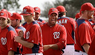**FILE** Washington Nationals pitcher Livan Hernandez, center, laughs with teammates during a spring training baseball workout Thursday, Feb. 17, 2011, in Viera, Fla. (AP Photo/David J. Phillip)