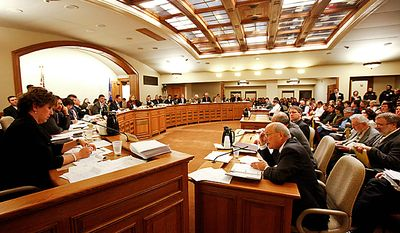 Wisconsin state Rep. Jennifer Shilling (left), a Democrat, questions Bob Lang (seated at desk), director of the Wisconsin Legislative Fiscal Bureau, on Wednesday, Feb. 16, 2011, at the state Capitol in Madison, Wis., during a joint Finance Committee meeting. (AP Photo/Andy Manis)