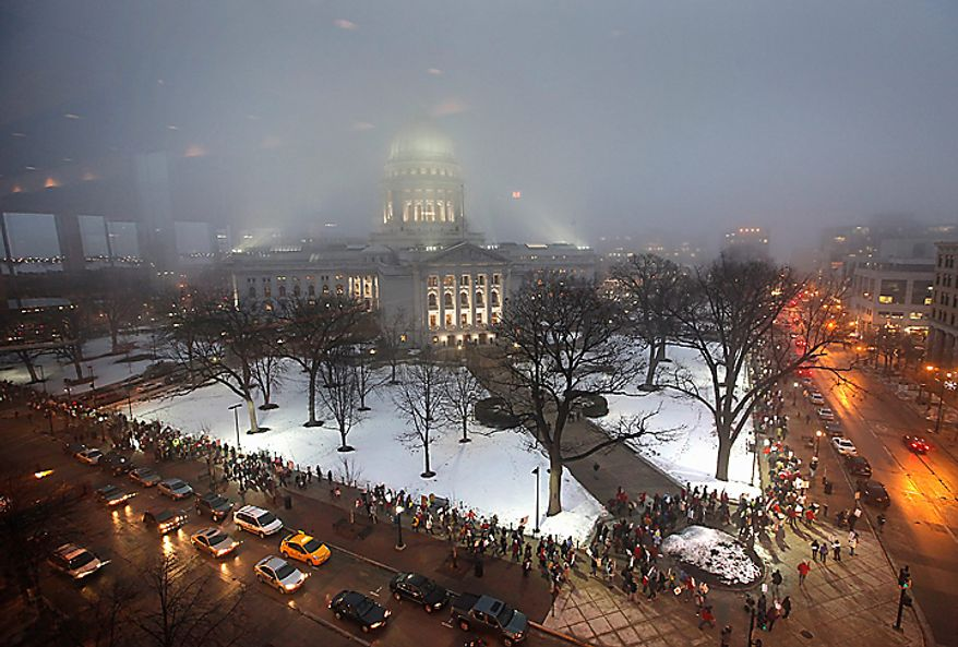 Opponents of Wisconsin Gov. Scott Walker's budget repair bill march around the state Capitol in Madison, Wis., on Wednesday, Feb. 16, 2011, the second day of widespread demonstrations. (AP Photo/Wisconsin State Journal, John Hart)