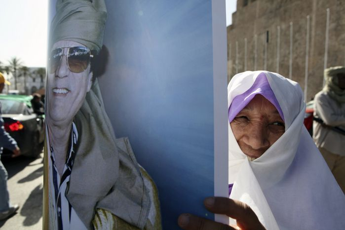 A Libyan pro-Gadhafi supporter displays a poster with his image during a march supporting leader Moammar Gadhafi in Tripoli, Libya, on Thursday Feb.17, 2011. (AP Photo