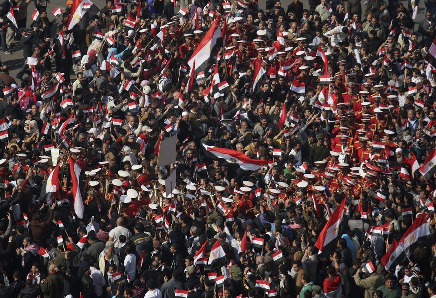 A brass band marches surrounded by demonstrators as people gathers for Friday prayers followed by a demonstration in Tahrir square, Cairo, Egypt, Friday Feb. 18, 2011. (AP Photo/Khalil Hamra)