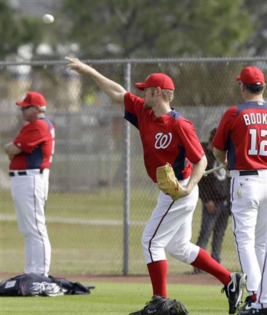 Washington Nationals right fielder Bryce Harper holds a football as part of a drill as he waits to chase a fly ball during a spring training baseball workout Tuesday, Feb. 22, 2011, in Viera, Fla. (AP Photo/David J. Phillip)