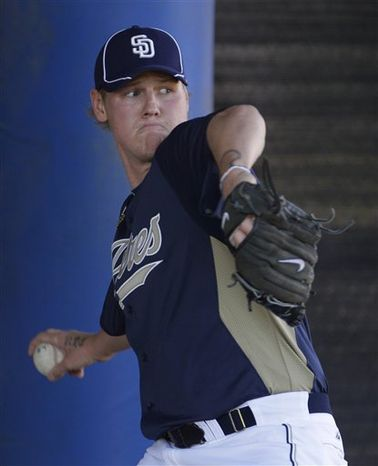 San Diego Padres' Ryan Ludwick, right, swings a bat as he gets ready for batting practice during baseball spring training Monday, Feb. 21, 2011, in Peoria, Ariz. (AP Photo/Charlie Riedel)