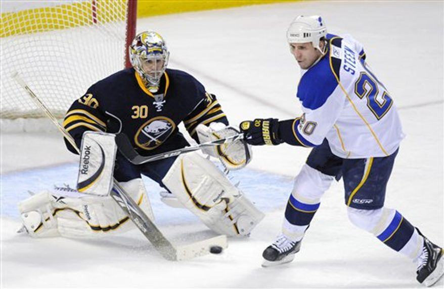 Buffalo Sabres goalie Ryan Miller, left, watches the puck as St. Louis Blues center looks to re-direct the shot during the third period of an NHL hockey game in Buffalo, N.Y., on Friday, Feb. 18, 2011. St. Louis won 3-0. (AP Photo/Don Heupel)
