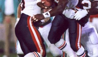 FILE - In this Aug. 14, 1989, file photo, Chicago Bears safety Dave Duerson (22) scrambles for running room after intercepting a pass as Miami Dolphins Jeff Uhlenhake (63) grabs hold during an NFL football game in Miami. Duerson, a four-time Pro Bowl safety who played on Super Bowl winners with the Chicago Bears and New York Giants, has died. He was 50.  Miami-Dade Police Detective Robert Williams says Duerson's body  was found Thursday in Sunny Isles Beach, Fla. Investigators have not determined the cause of death.  (AP Photo/File)