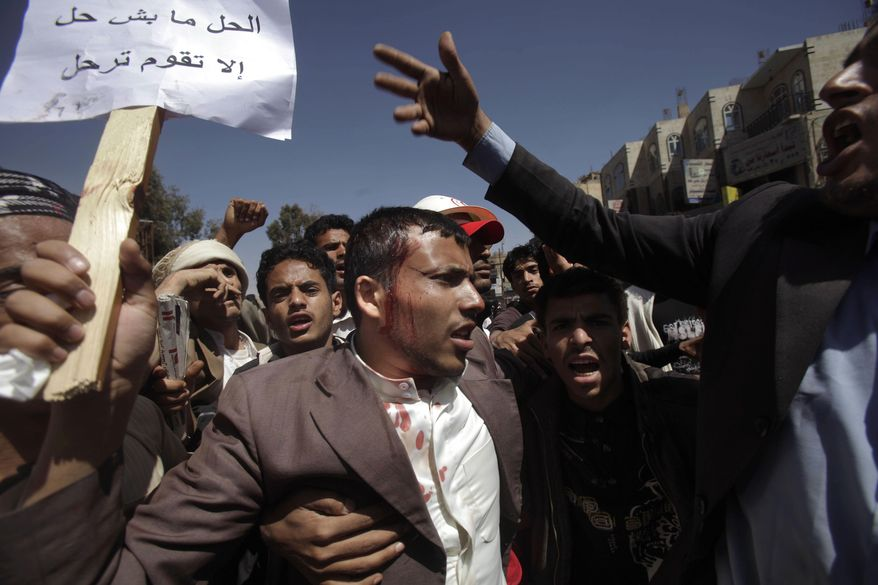 A wounded anti-government demonstrator is helped by other demonstrators after being hit by a stone thrown by Yemeni government supporters during clashes in Sanaa, Yemen, on Saturday, Feb. 19, 2011. Hundreds of Yemenis began demonstrating early in the morning Saturday outside the university in Sanaa, demanding the ouster of the country's longtime ruler as they marched toward the Justice Ministry. (AP Photo/Muhammed Muheisen)