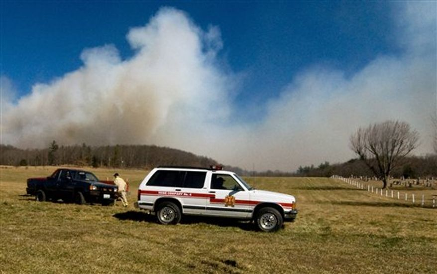 Firefighters are stationed on a hill below a 300-acre wildfire in the woods off of Rawley Pike near Harrisonburg, Va., on Saturday, Feb. 19, 2011. (AP Photo/Daily News-Record, Traci White)