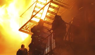 Firefighters stand on a fire escape as winds whip the flames from a five-alarm fire in the Brooklyn borough of New York late on Saturday, Feb. 19, 2011. The strong winds meant several hours of work for hundreds of New York firefighters trying to extinguish the fire, which ripped through the six-story apartment building. At least 20 firefighters were injured, authorities said. (AP Photo/Paul Martinka)