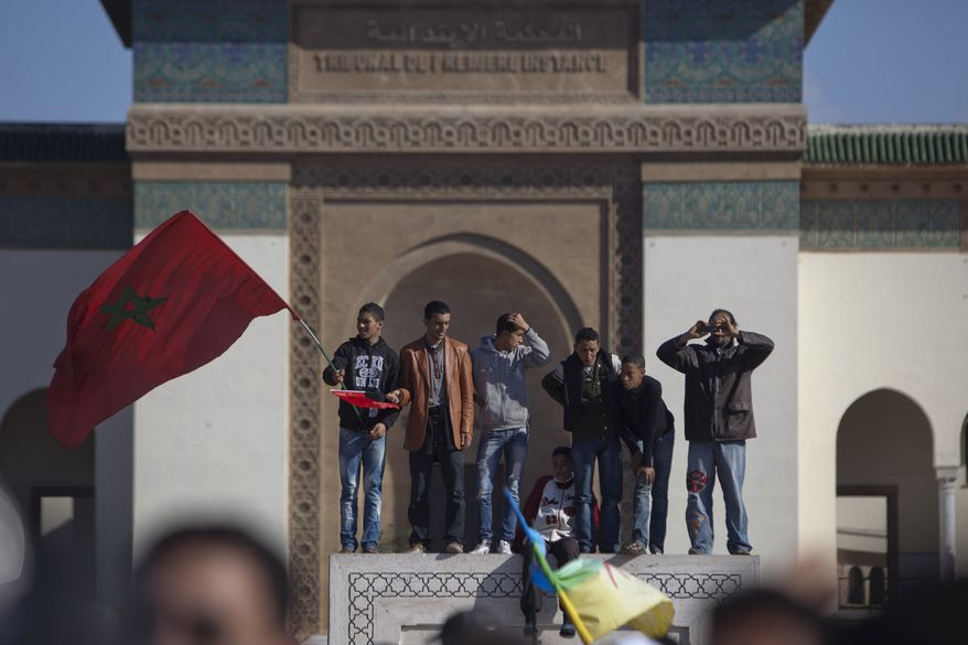A protester holds the Moroccan flag during a demonstration on Sunday in Casablanca, Morocco. Thousands of people marched in cities across Morocco, demanding a new constitution to bring more democracy in the North African kingdom amid the wave of Arab world upheaval. (Associated Press)