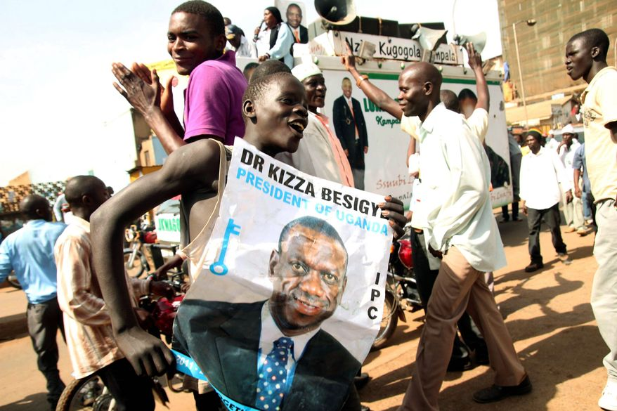 A supporter of opposition leader Kizza Besigye displays his poster during a protest in the city of Kampala, Uganda, on Sunday. Uganda's longtime president has won another term, the country's election commission said Sunday, but the top opposition leader alleged the election was fraudulent and vowed to reject the results. (Associated Press)